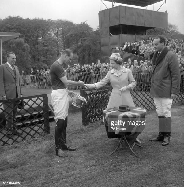 Queen Elizabeth II presents the Royal Windsor Horse Show Cup to her husband the Duke of Edinburgh who as captain of Windsor Park had helped defeat...