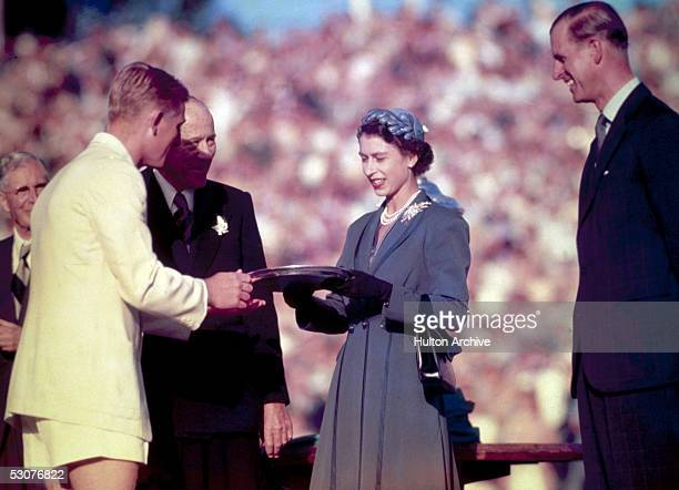Queen Elizabeth II presents the Silver Salver to Australian tennis champion Lewis Hoad at Centre Court, Kooyong, during her trip to Australia, 1954....