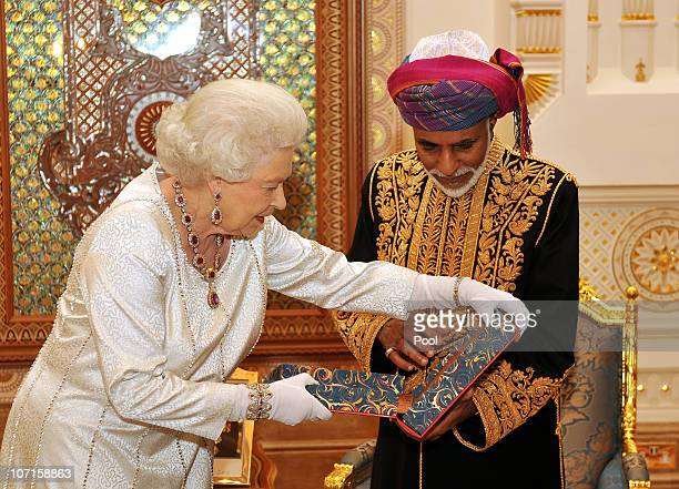 Queen Elizabeth II presents the Sultan of Oman His Majesty Sultan Qaboos bin Said with a book before a State Banquet at his Palace on November 26...