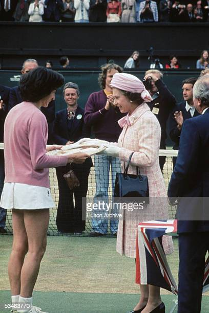 Queen Elizabeth II presents the trophy to British tennis player Virginia Wade after she won the Women's Singles competition at Wimbledon 1st July 1977