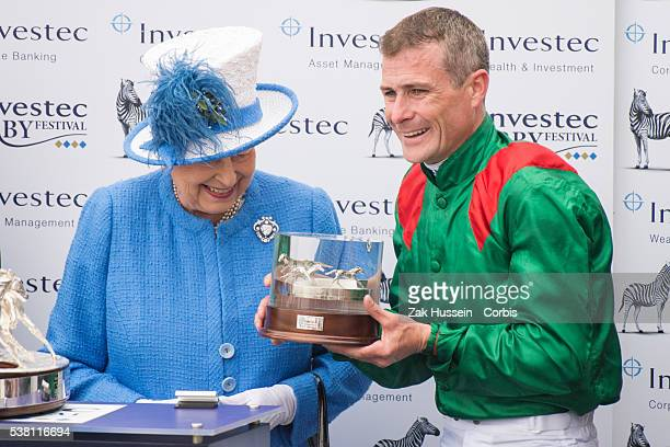 Queen Elizabeth II presents the trophy to Epsom Derby winning jockey Pat Smullen during the Investec Derby Festival at Epsom Racecourse on June 4...