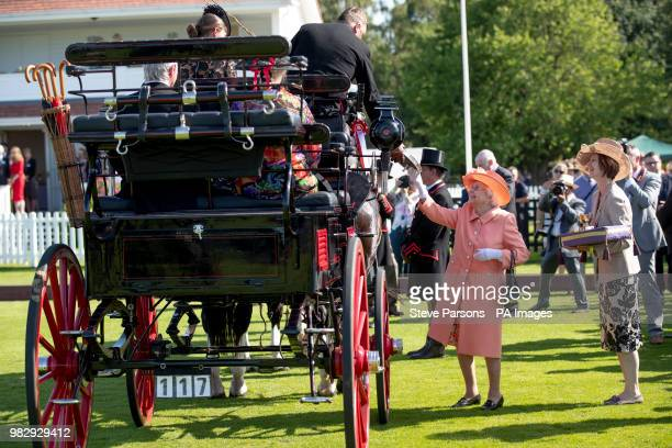 Queen Elizabeth II presents trophies to the winners of the OutSourcing Royal Windsor Cup final at the Guards Polo Club Windsor Great Park Egham Surrey