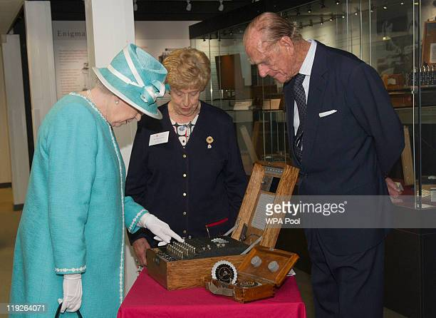 Queen Elizabeth II presses the button to start the enigma code breaking machine as Prince Philip Duke of Edinburgh and wartime operator Ruth Bourne...