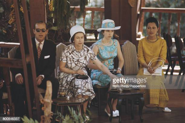 Queen Elizabeth II Prince Philip Mountbatten Duke of Edinburgh and Princess Anne pictured seated with Queen consort Sirikit of Thailand in Bangkok...