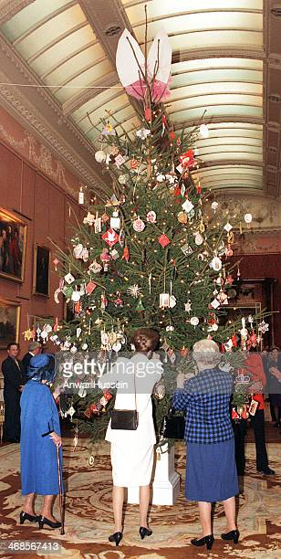 Queen Elizabeth II, Princess Anne, the Princess Royal and Queen Elizabeth, The Queen Mother admire Christmas decorations on the Christmas tree in the...