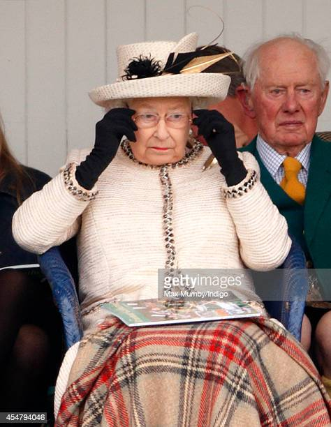 Queen Elizabeth II puts on her glasses as she attends the Braemar Gathering at the The Princess Royal and Duke of Fife Memorial Park on September 6...