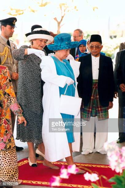 Queen Elizabeth II Putting On A Special Coat In Order To Enter The Jame'asr Hassanal Bolkiah Mosque In Brunei Diana Lady Farnham Her Ladyinwaiting Is...