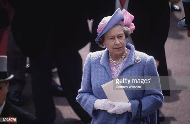 Queen Elizabeth II Queen of Great Britain wearing a blue coat with a pink and blue hat