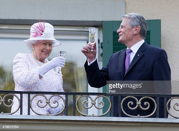 Queen Elizabeth II raises her glass with president of Germany Joachim Gauck as they attend a garden party at the British Embassy residence on day...