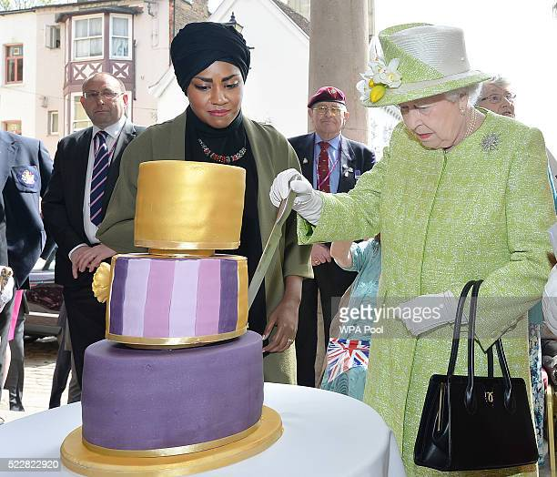 Queen Elizabeth II receives a birthday cake from Nadiya Hussain winner of the Great British Bake Off during her 90th Birthday Walkabout on April 21...