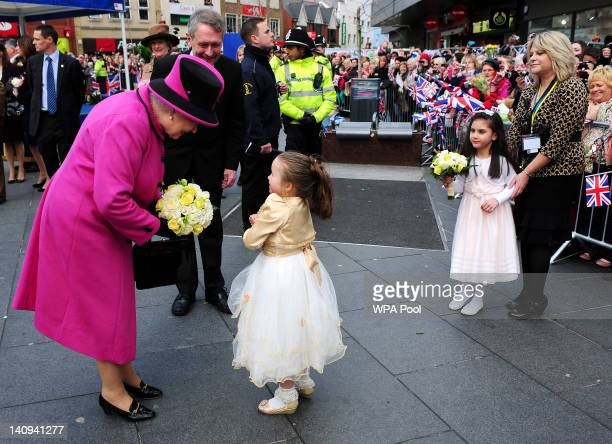 Queen Elizabeth II receives a bouquet of flowers during her visit to Leicester on March 8 2012 in Leicester England The royal visit to Leicester...