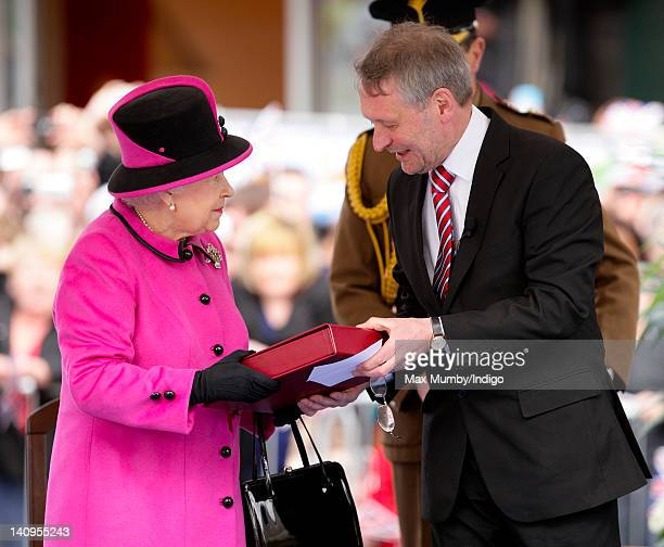 Queen Elizabeth II receives a gift as she accompanied by Prince Philip Duke of Edinburgh and Catherine Duchess of Cambridge visits Leicester on the...