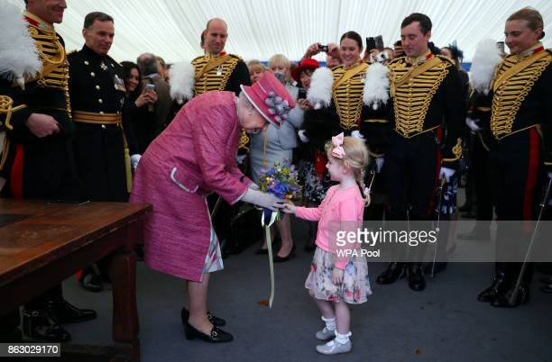 Queen Elizabeth II receives a posy from Tilly Beau Wildish during a reception following the King's Troop Royal Horse Artillery during their 70th...