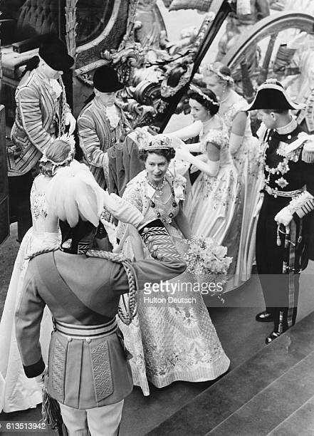 Queen Elizabeth II receives a salute from one of The Life Guards as her royal attendants help her out of her coach Her husband Duke Philip is to her...
