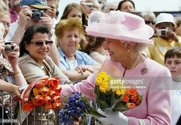 Queen Elizabeth II receives flowers during a walkabout on the promenade on July 20, 2005 in Dover, England. The Queen officially opened two passenger...