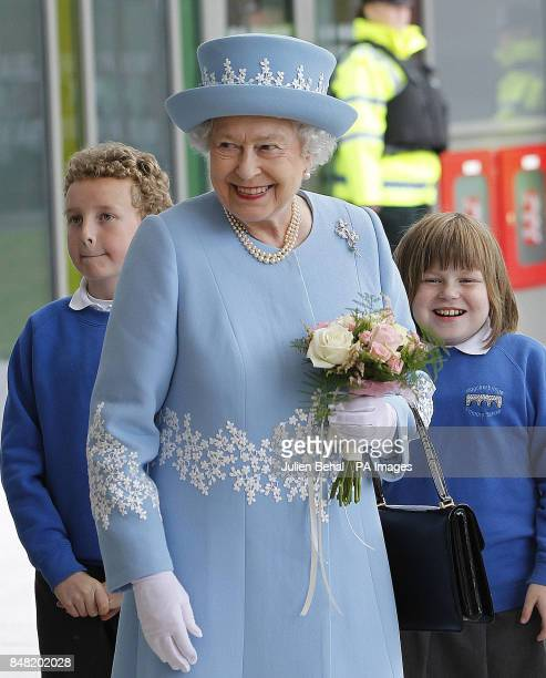 Queen Elizabeth II receives flowers from local school children after she visited South West Acute Hospital in Enniskillen County Fermanagh during a...
