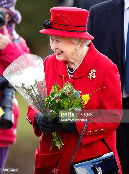 Queen Elizabeth II receives flowers from members of the public after attending Sunday service at the Church of St Peter St Paul West Newton on...