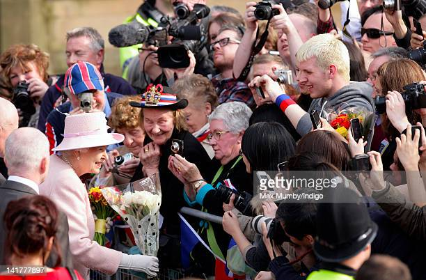 Queen Elizabeth II receives flowers from members of the public during a walkabout outside Manchester Town Hall on a visit to Manchester as part of...