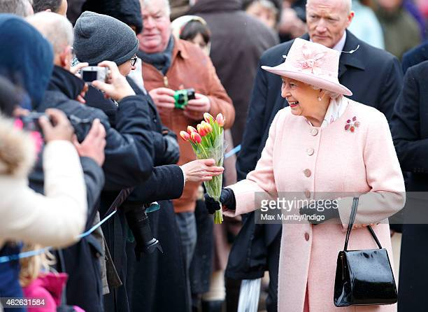 Queen Elizabeth II receives flowers from members of the public during a walkabout after attending Sunday service at the church of St Peter and St...