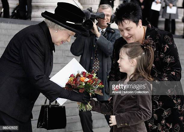 Queen Elizabeth II receives flowers from sevenyearold Ruby Grey whose father died in the blasts and they attend the National Memorial Service...