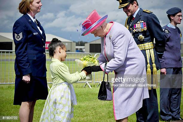 Queen Elizabeth II receives flowers from Soleece Anabwani, aged 6, at RAF Fairford, after presenting new Colours at the opening of the Royal...