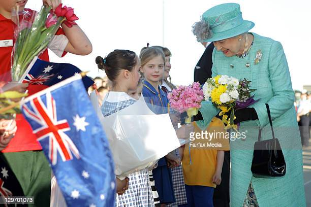 Queen Elizabeth II receives flowers from the public at her arrival on October 19, 2011 in Canberra, Australia. The Queen and Duke of Edinburgh are on...