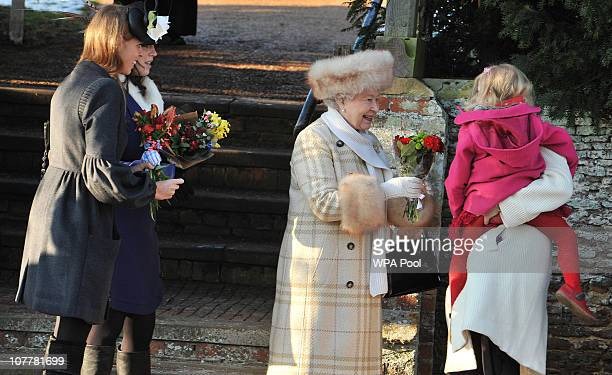 Queen Elizabeth II receives gifts as she attends the Christmas Day Church Service with other members of the Royal family at St Mary's Church on...