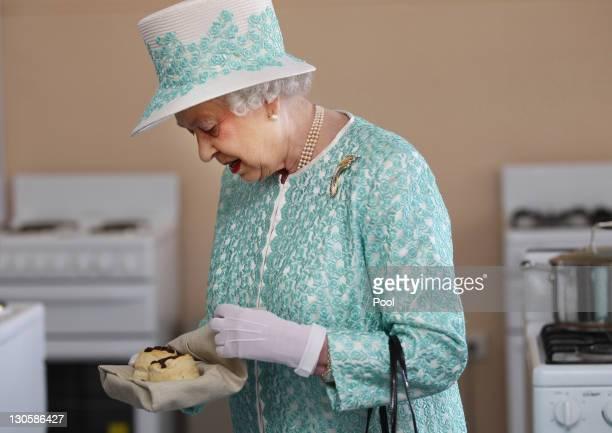 Queen Elizabeth II receives scones from the Clontarf kitchen during her visit to Clontarf Aboriginal college on October 27 2011 in Perth Australia...
