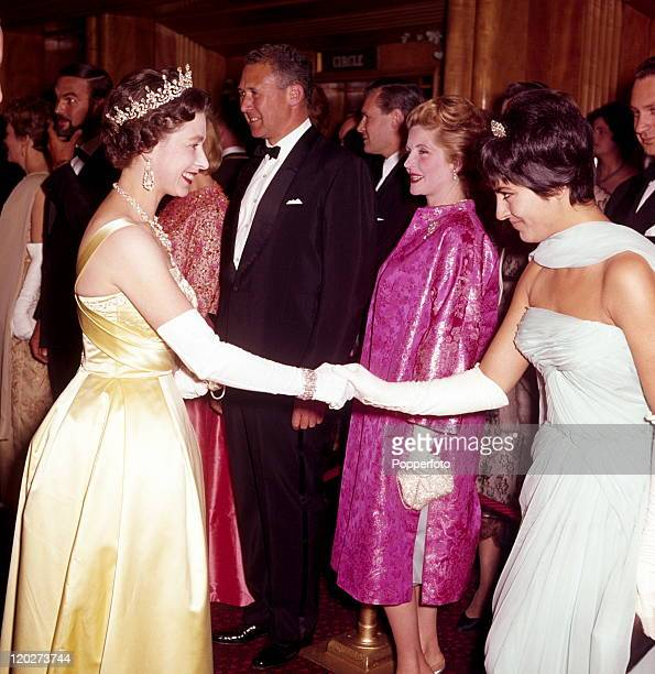 Queen Elizabeth II receives the Italian actress Gia Scala after the premiere of 'The Guns of Navarone' at the Odeon Theatre London on 27th April 1961...