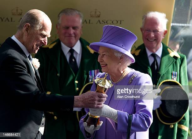 Queen Elizabeth II receives the winners trophy from Prince Philip Duke of Edinburgh after her horse Estimate wins the Queen's Vase during Royal Ascot...