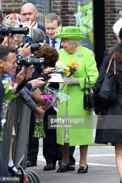 Queen Elizabeth II recieves flowers as she and the Duchess of Sussex walk from Storyhouse to Chester Town Hall on June 14 2018 in Chester England...