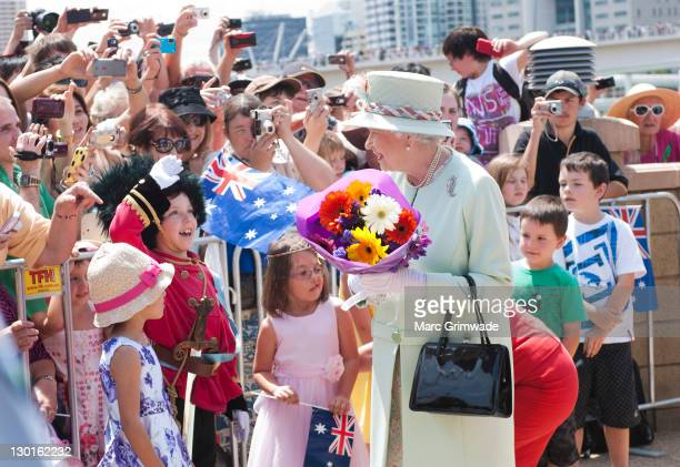 Queen Elizabeth II recieves flowers from children at Southbank on October 24 2011 in Brisbane Australia The Queen and Duke of Edinburgh are on a...