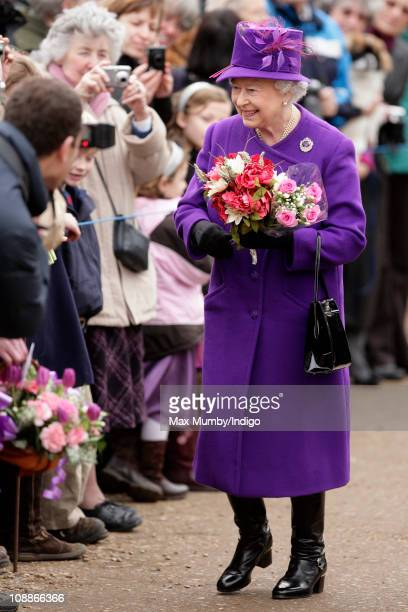 Queen Elizabeth II recieves flowers from members of the public during a walkabout after attending a church service on the 59th anniversary of her...