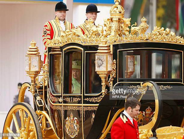 Queen Elizabeth II rides a carriage with Colombia's President Juan Manuel Santos as they depart his ceremonial welcome at Horse Guards Parade on...
