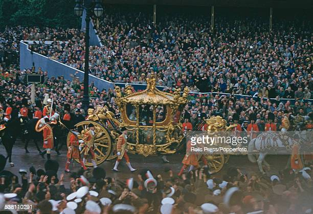 Queen Elizabeth II rides in the Gold State Coach past crowds of spectators on tiered viewing stands near Admiralty Arch and Trafalgar Square during...