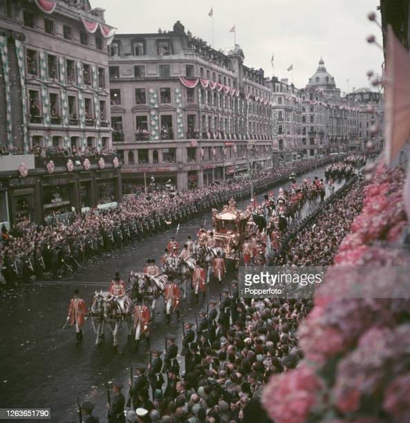 Queen Elizabeth II rides in the Gold State Coach past crowds of spectators lining Regent Street during her Coronation procession around the West End...