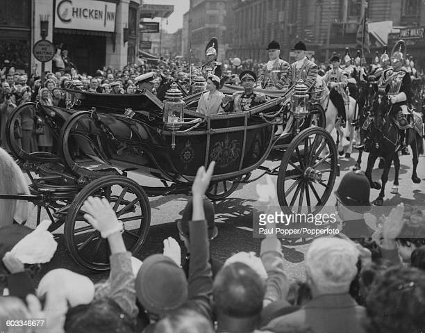 Queen Elizabeth II rides in the State Coach with Mohammad Reza Pahlavi Shah of Persia and Prince Philip Duke of Edinburgh along Victoria Street from...