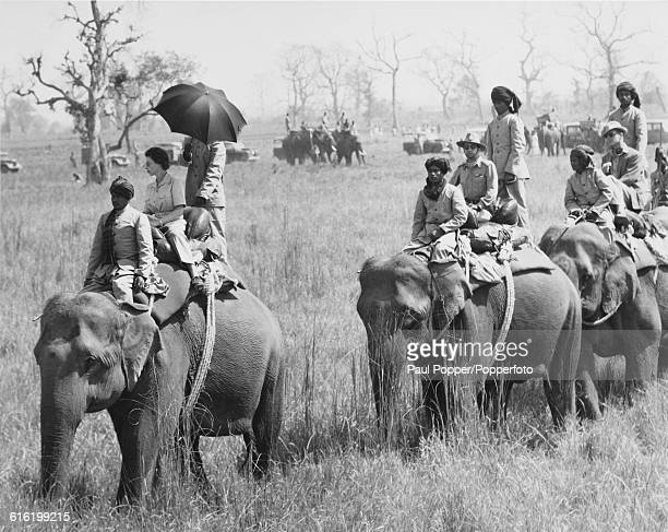 Queen Elizabeth II rides on the back of a lead elephant with a procession of elephants carrying King Mahendra of Nepal and Prince Philip Duke of...