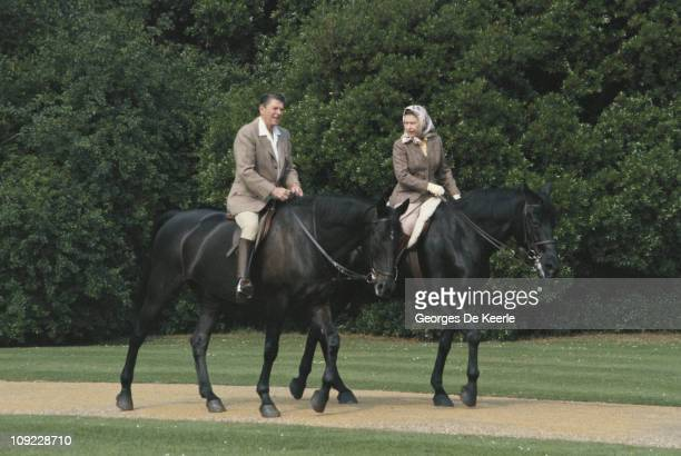 Queen Elizabeth II riding in the grounds of Windsor Castle with US President Ronald Reagan during his state visit to the UK 8th June 1982 She is...