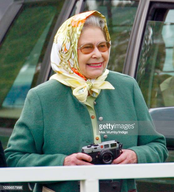 Queen Elizabeth II seen holding her Leica camera as she watches Prince Philip Duke of Edinburgh compete in the Driven Dressage element of the...