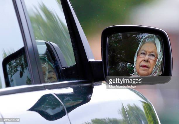 Queen Elizabeth II seen reflected in the wind mirror of her Range Rover car as she drives around the Royal Windsor Horse Show in Home Park on May 12...
