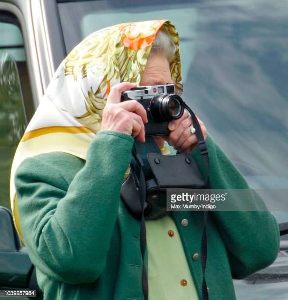 Queen Elizabeth II seen taking photographs of Prince Philip Duke of Edinburgh as he competes in the Driven Dressage element of the Carriage Driving...