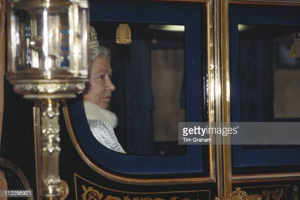 Queen Elizabeth II seen through the window of her horsedrawn carriage on her arrival at the State Opening of Parliament at the House Of Lords London...