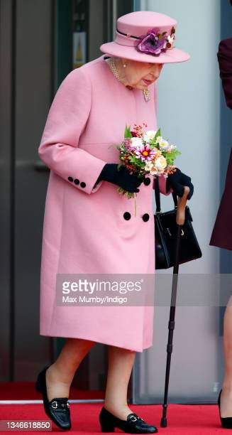 Queen Elizabeth II seen using a walking stick as she attends the opening ceremony of the sixth session of the Senedd at The Senedd on October 14,...