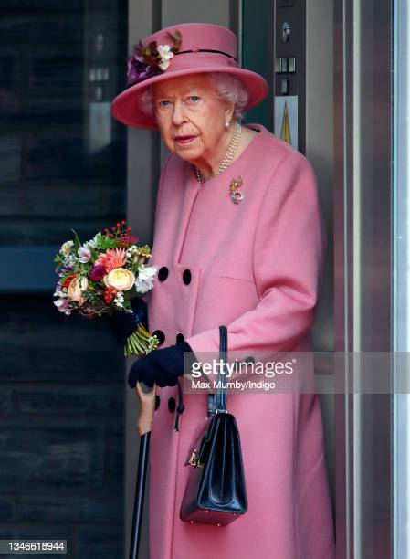 Queen Elizabeth II seen using a walking stick as she steps out of an elevator after attending the opening ceremony of the sixth session of the Senedd...