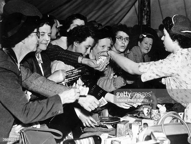 Queen Elizabeth II selling an item at a sale of work at Abergeldie Castle, near Balmoral, to raise funds for the rebuilding of the vestry at Crathie...
