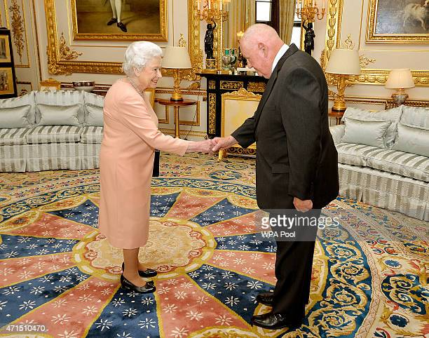 Queen Elizabeth II shakes hands with American businessman John Mars as she presents him with an honorary Knighthood at Windsor Castle on April 29,...
