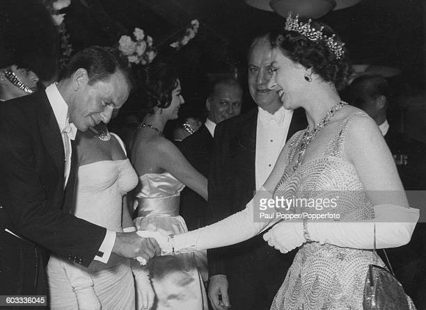 Queen Elizabeth II shakes hands with American singer and actor Frank Sinatra as she meets the stars attending the premiere of the Danny Kaye film 'Me...