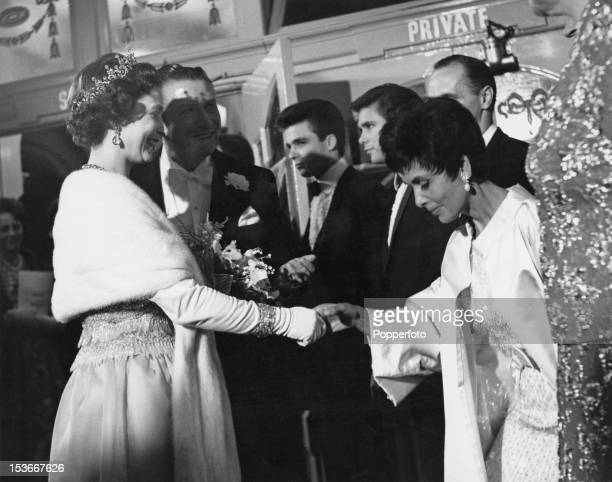 Queen Elizabeth II shakes hands with American singer Lena Horne at the Royal Variety Performance at the London Palladium, 2nd November 1964. Left to...