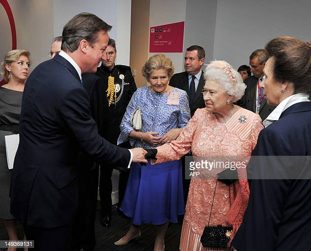 Queen Elizabeth II shakes hands with British Prime Minister David Cameron as Princess Anne the Princess Royal looks before attending the Olympic...